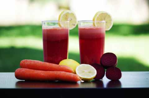 carrot fruit beside lemon fruit on black wooden table